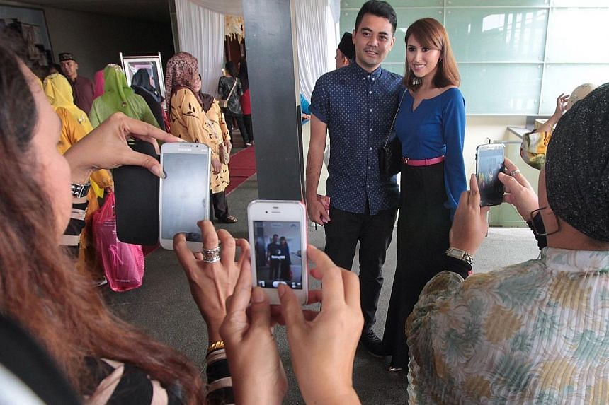 Guests at the wedding take photographs of actress Nurul Aini (right, in blue) who was present at the wedding reception. -- ST PHOTO: NEO XIAOBIN