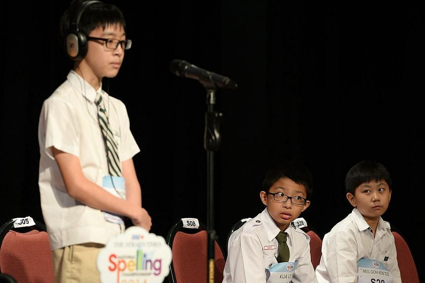 2nd-placed Kua Le Yi (centre) and third-placed Neil Goh Ken Tze (right) watch as Thomas Egan Ang Yi Ren, who was eventually placed first, spells a word at the ST-MOE National Spelling Championships zonal rounds (South Zone). -- ST PHOTO: NG SOR LUAN
