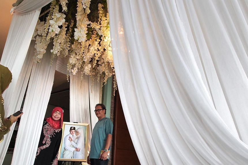 Guests take photographs with a portrait of the couple outside the reception hall.-- ST PHOTO: NEO XIAOBIN