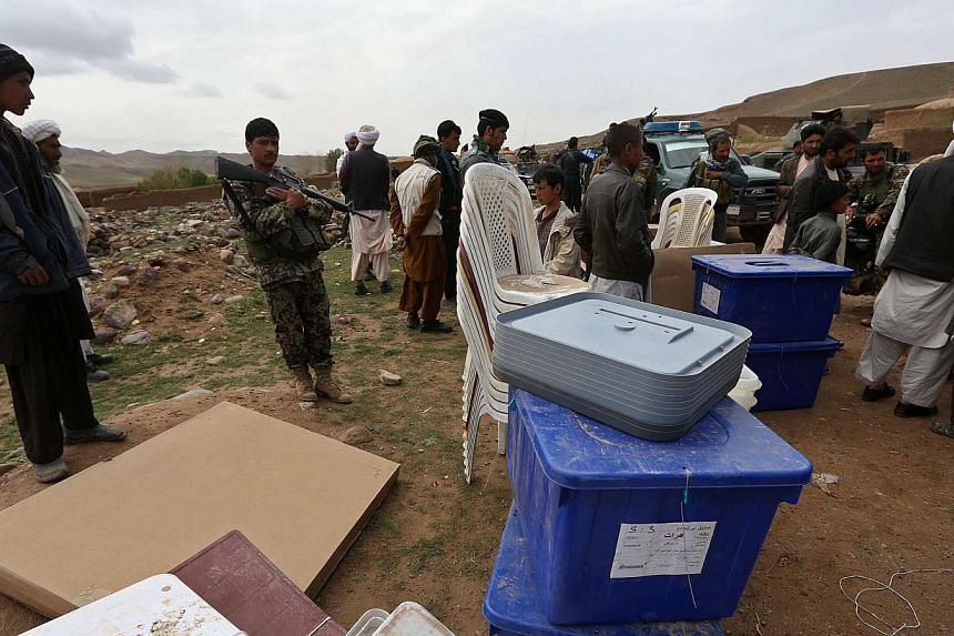 Afghan election commission workers unload ballot boxes form a vehicle at Mir Abadi village in Adraskan district of Herat Province on April 4, 2014. -- PHOTO: REUTERS