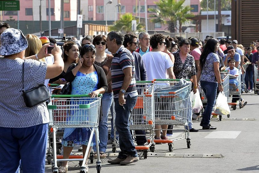 People queue at a major grocery store in Iquique 1,950 km north of Santiago on April 3, 2014. Life was gradually returning to normal in northern Chile on Friday, with power restored to a majority of homes that lost electricity during this week's powe