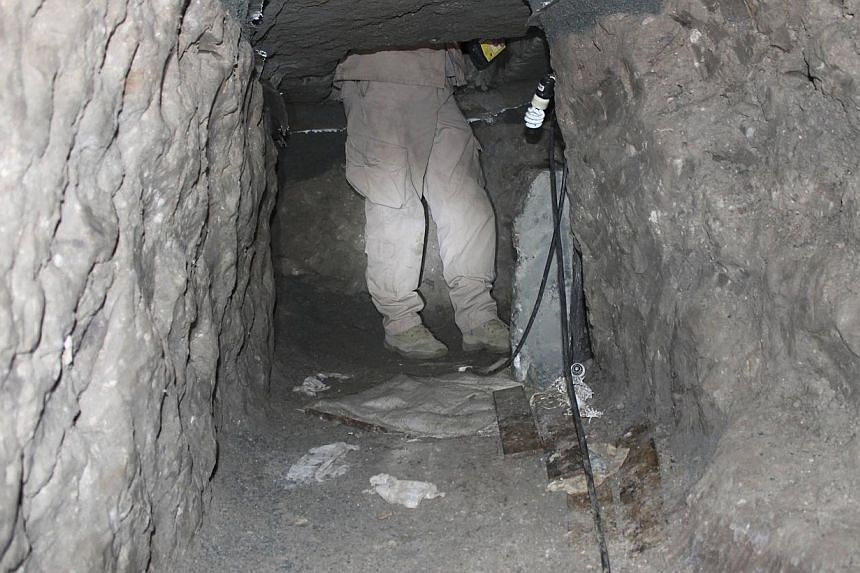 A law enforcement officer enters a drug tunnel found in a warehouse in Otay Mesa, California on April 3, 2014, in this handout photo released to Reuters on April 4, 2014.US investigators said on Friday they have uncovered two sophisticated drug