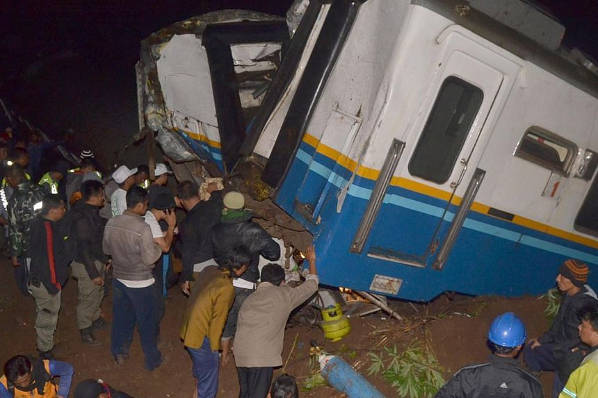 Rescuers search for victims on the carriages of a derailed train in Tasikmalaya on the Indonesian island of Java on April 4, 2014. -- PHOTO: AFP