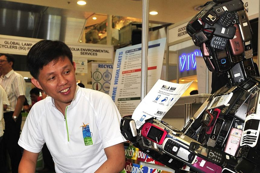 """Mr Chan Chun Sing, Minister of Social and Family Development, Second Minister for Defence and Grassroots Adviser for Tangong Pagar, admiring a figure made out of recycled mobile phone parts dubbed """"Nokia Man"""". -- ST PHOTO:DIOS VINCOY JR"""