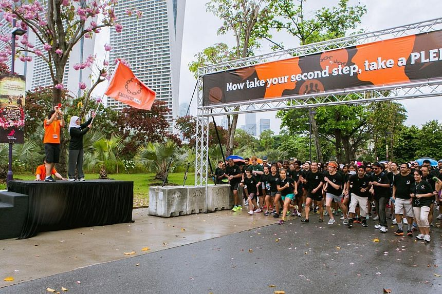 Madam Halimah Yacob (second, left) flags off participants at Steps in the Park. Around 1,200 people braved the rain on Saturday morning to take part in a 5km run or walk to raise awareness about human trafficking. -- PHOTO: DARRYL CHAN
