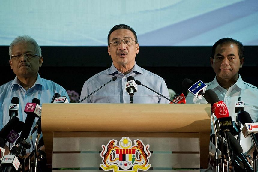 Malaysian Minister of Defence and Acting Transport Minister Hishammuddin Hussein (centre) delivers a statement to the media on the missing Malaysia Airlines flight MH370 at the Putra World Trade Center (PWTC) in Kuala Lumpur on April 5, 2014. -- PHOT