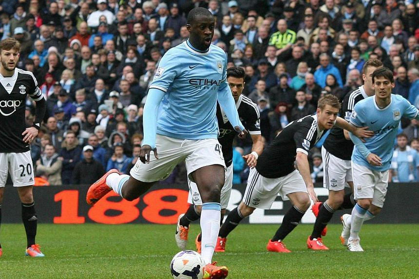 Manchester City's Ivorian midfielder Yaya Toure scores the opening goal from a penalty against Southampton during the English Premiership League football match between Manchester City FC and Southampton FC at the Etihad stadium in Manchester, north w