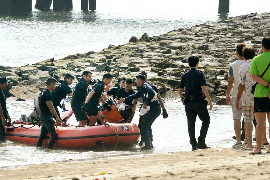 Rescue personnel bringing the body of a 35-year-old medium to shore. The body of a temple medium was found in the sea off Changi Beach Park on Sunday morning, hours after he performed rites as part of the Qing Ming Festival. -- ST PHOTO: SH