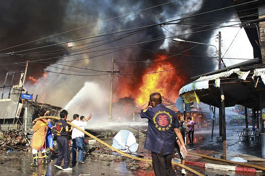 Rescue workers extinguish a fire at the site of a bomb blast in southern Thailand's Yala province April 6, 2014. One person was killed and 14 wounded on Sunday in a series of apparently co-ordinated blasts - including a car bomb - in a major tow