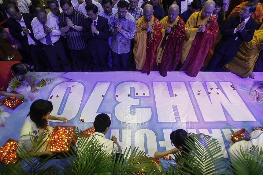 """People place candles on a banner reading, """"Pray for MH370"""" after a special prayer for passengers onboard the missing Malaysia Airlines flight MH370 at the Malaysian Chinese Association (MCA) headquarters in Kuala Lumpur April 6, 2014.Malaysia A"""