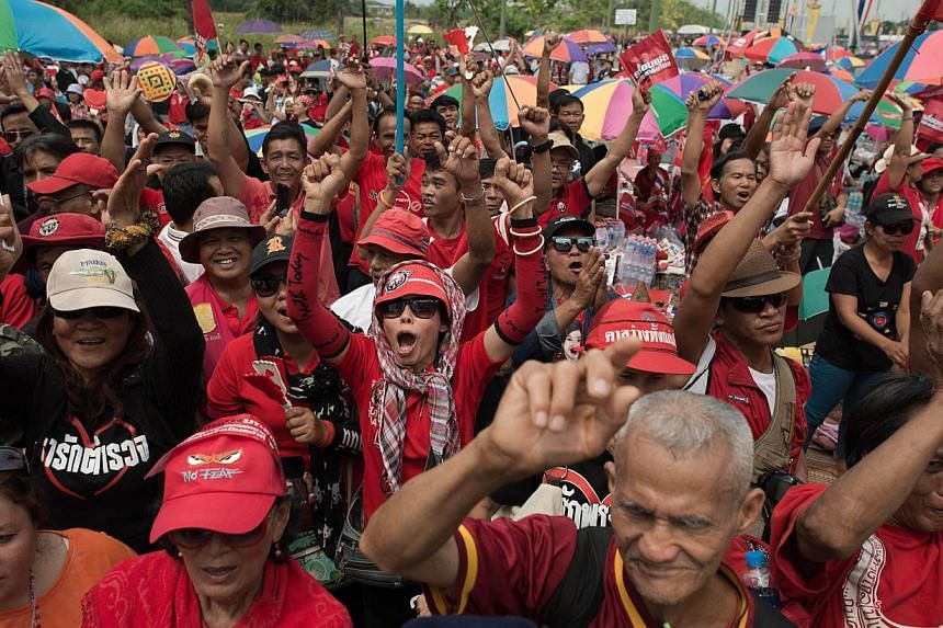 Thailand's pro-government Red Shirt supporters rallied for a second day on Sunday, vowing to protect Prime Minister Yingluck Shinawatra, who is facing a slew of legal challenges that could see her toppled within weeks. -- PHOTO: AFP