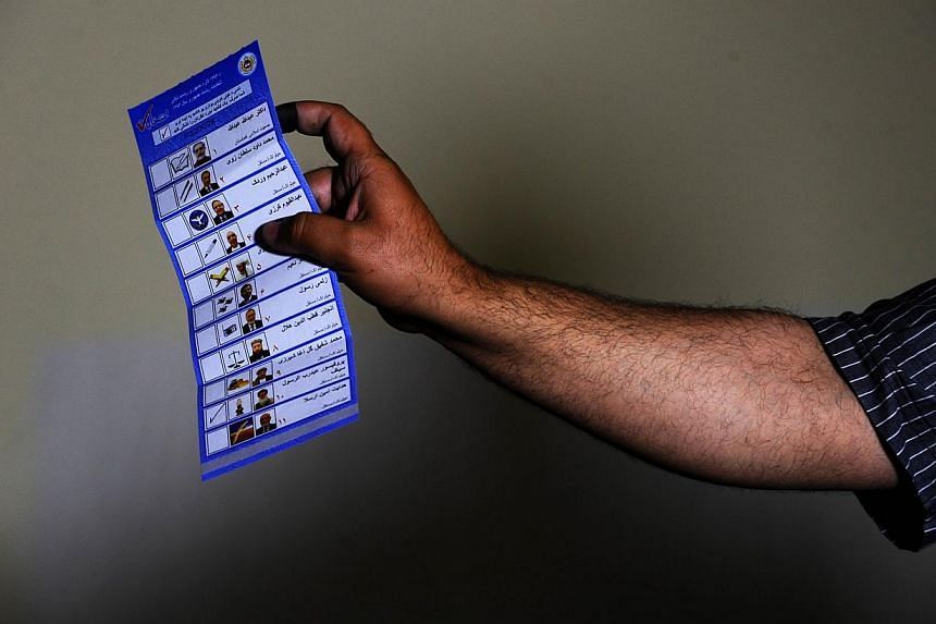 An Afghan election worker shows a ballot to the elections observers while counting the votes after a polling station was closed for voting in the north-western city of Herat on April 5, 2014. -- PHOTO: AFP