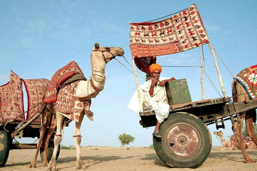 In this file photograph taken on September 5, 1999, an election worker lights a cigarette as he sits in a camel-drawn mobile polling station in India's Thar desert during the first round of voting during month-long staggered elections. In India's ele