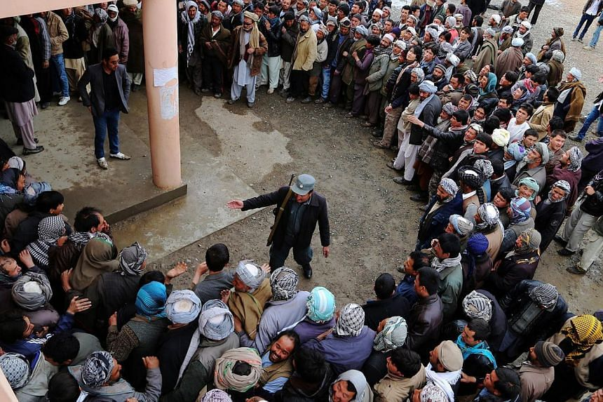 An Afghan policeman tries to keep order as voters wait in line outside a polling station inBamiyan on April 5, 2014. Afghan voters went to the polls to choose a successor to President Hamid Karzai, braving Taliban threats in a landmark election held