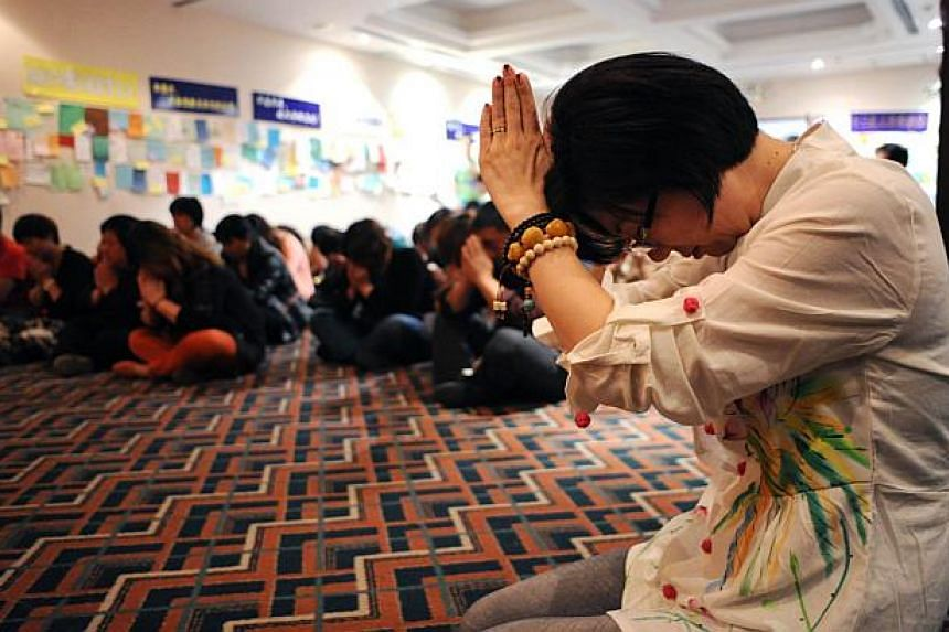 Chinese relatives of passengers on the missing Malaysia Airlines flight MH370 pray after a meeting in a pray room at the Metro Park Hotel in Beijing on April 4, 2014. The hunt for physical evidence that the Malaysia Airlines jet crashed in the Indian