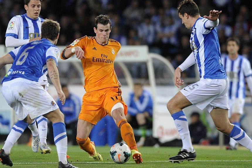 Real Madrid's Welsh striker Gareth Bale (centre) vies with Real Sociedad's midfielder Markel Bergara (left) and defender Ion Ansotegi (right) during the Spanish league football match against Real Sociedad at the Anoeta stadium in San Sebastian on Apr
