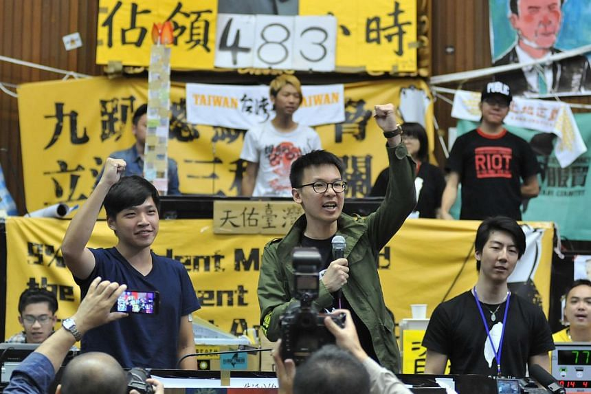 Student protest leaders Chen Wei-ting (front left) and Lin Fei-fan (right) shouting slogans inside Parliament as more than 200 protesters -- mostly students -- occupy the building in Taipei on April 6, 2014. Student protesters have occupied parliamen