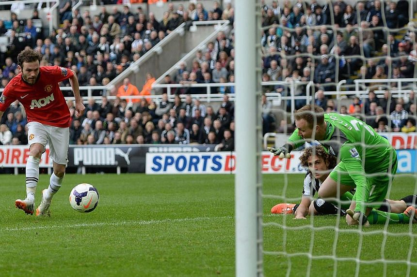 Manchester United's Juan Mata (left) shoots to score his second goal during their English Premier League match against Newcastle United at St James' Park on April 5, 2014. -- PHOTO: REUTERS