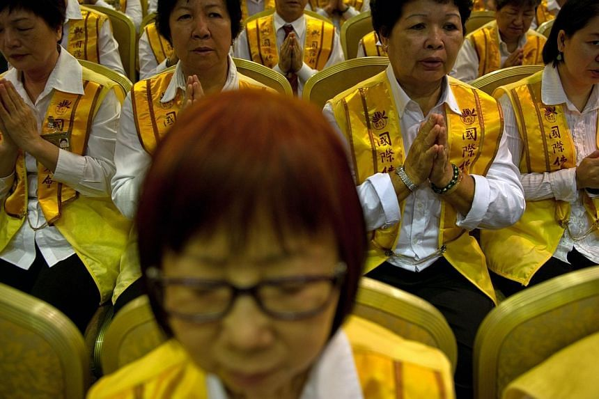 Malaysian Buddhists offer prayers for passengers onboard missing Malaysia Airlines (MAS) flight MH370 in Kuala Lumpur on April 6, 2014. -- PHOTO: AFP