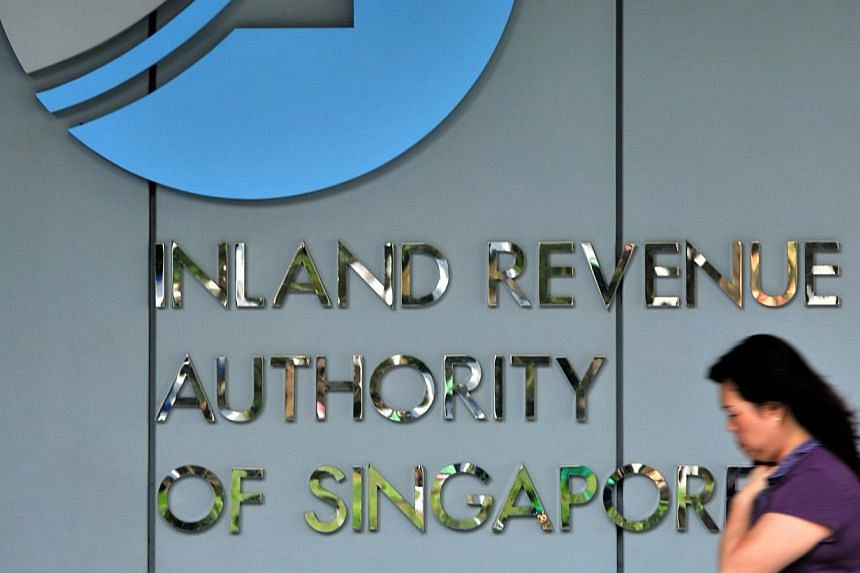 A woman walking past the logo of Inland Revenue Authority of Singapore at Revenue House. -- ST FILE PHOTO: KUA CHEE SIONG