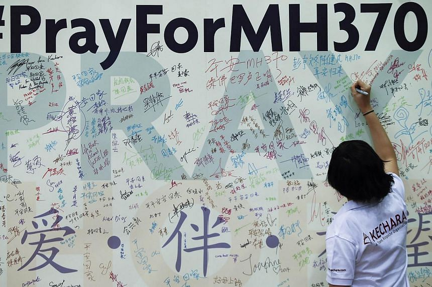A woman writes a message on a board for family members of passengers onboard the missing Malaysia Airlines Flight MH370 at the Malaysian Chinese Association headquarters in Kuala Lumpur on April 6, 2014. -- PHOTO: REUTERS