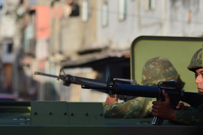 Brazilian soldiers patrolling the street during security operations in Vila Pinheiro, part of the Mare shantytown complex near the Galeao international airport in the northern suburb of Rio de Janeiro on April 5, 2014. -- PHOTO: AFP