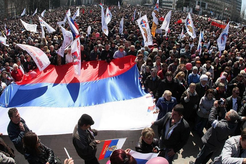 Pro-Russian protesters hold Russian national flags during the rally in eastern Ukrainian city of Donetsk on Sunday, April 6, 2014. About 50 pro-Russian protesters broke through police lines on Sunday and stormed inside the main administration bu