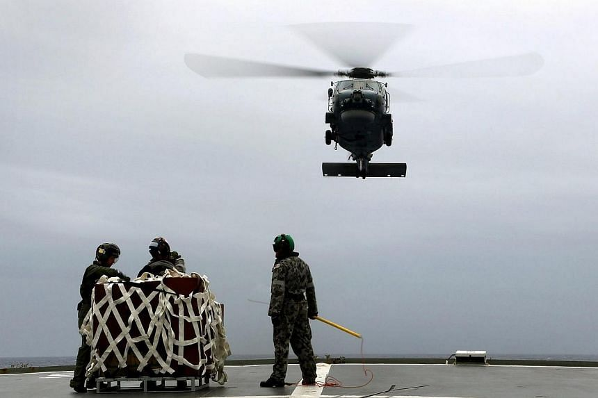 A S-70B-2 Seahawk (Tiger 75) helicopter makes an approach to the flight deck of Australian Navy ship HMAS Toowoomba to pick up supplies during a vertical replenishment at sea with HMAS Success as they continue to search for the missing Malaysian Airl