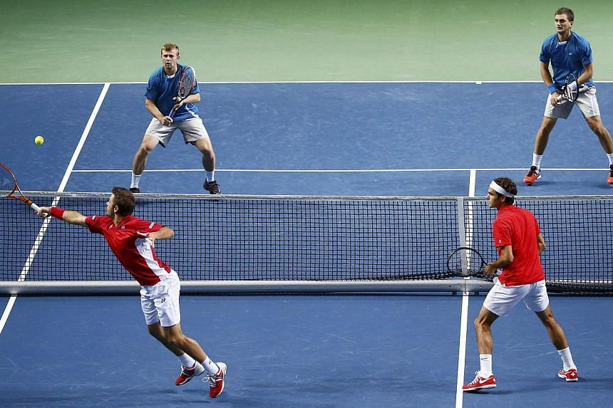 Switzerland's Stanislas Wawrinka (bottom left) returns a ball next to Roger Federer (bottom right) during their Davis Cup quarter-final tennis match against Andrey Golubev (top left) and Aleksandr Nedovyvesov of Kazakhstan in Geneva on April 5, 2014.