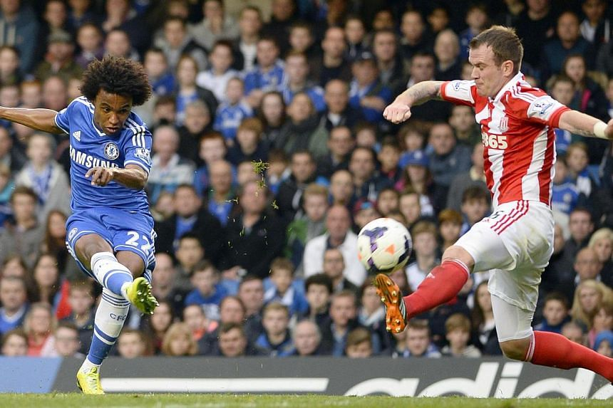 Chelsea's Willian (left) takes a shot as he is challenged by Stoke City's Glenn Whelan during their English Premier League match at Stamford Bridge on April 5, 2014. -- PHOTO: REUTERS