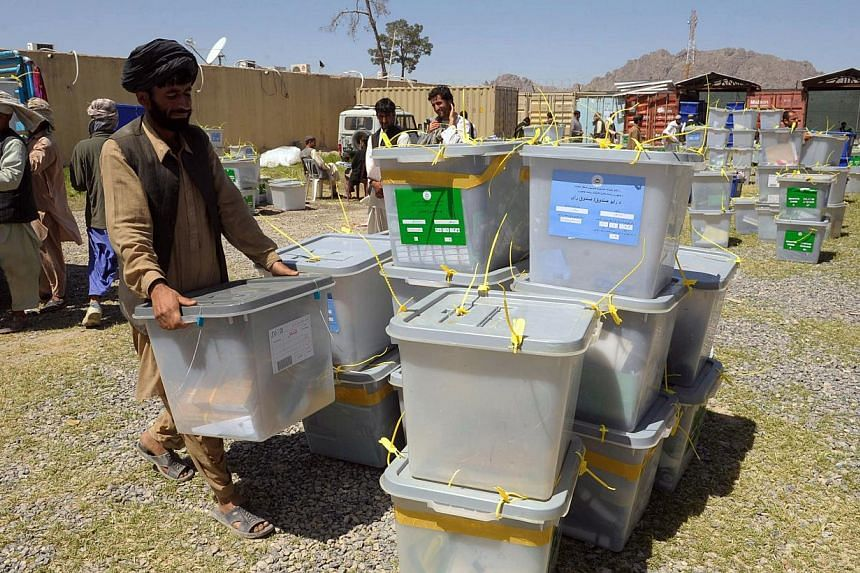 Afghan election commission workers unload ballot boxes at the IEC (Independent Election Commission) in Kandahar on April 7, 2014. Preliminary tallies from Afghanistan's presidential election showed former foreign minister Abdullah Abdullah leadi