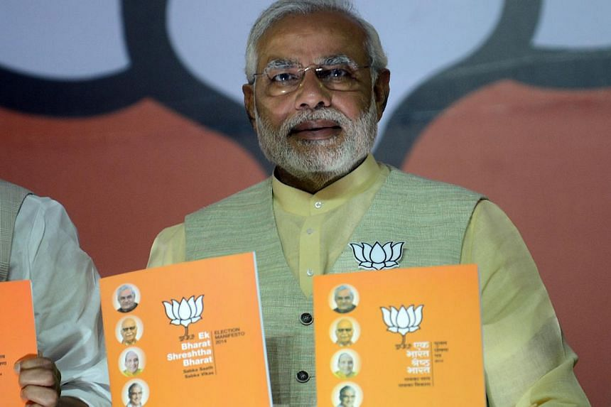 India's Bharatiya Janata Party (BJP) Prime Ministerial candidate Narendra Modi poses with the party manifesto upon its release in New Delhi on April 7, 2014, on the opening day of voting in national elections. -- PHOTO: AFP