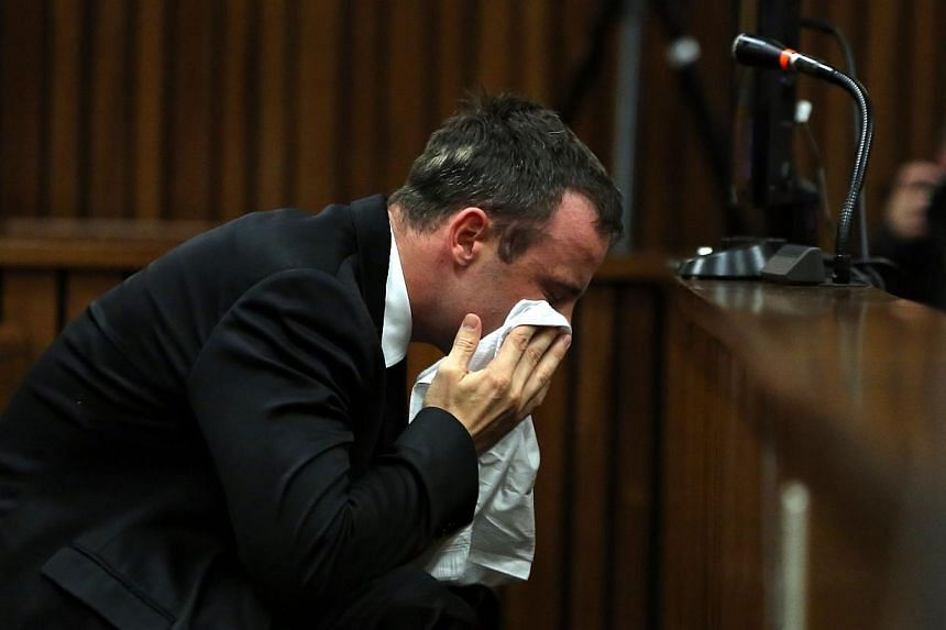 South African Paralympic track star Oscar Pistorius wipes his face during his trial in Court in Pretoria on April 7, 2014. -- PHOTO: AFP