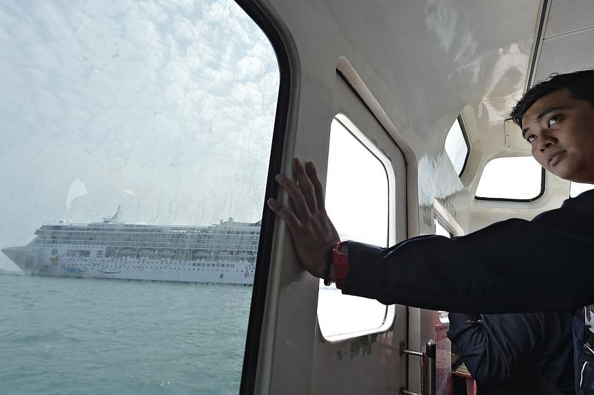 ICA officer Hizar Zahir, 29, approaching a cruise ship to check passengers' passports under the clearance-on-board system. The authority is working on a portable device to allow for electronic checks of passports.