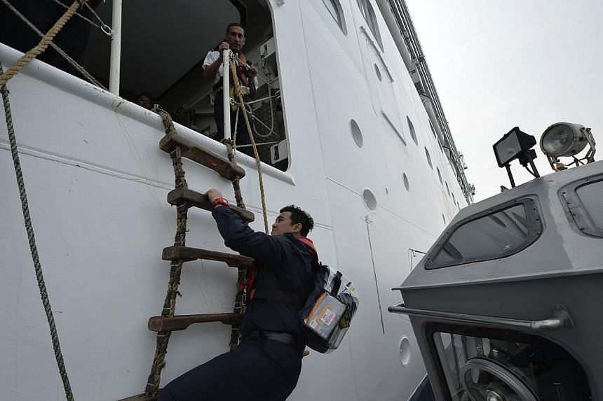 Sergeant Hizar Zahir, 29, one of the ICA officers, boarding Superstar Virgo using a pilot ladder in order to pre-clear cruise passengers.  Embarkation officers with the Superstar Virgo helping to arrange  passports by nationality, and channel them to