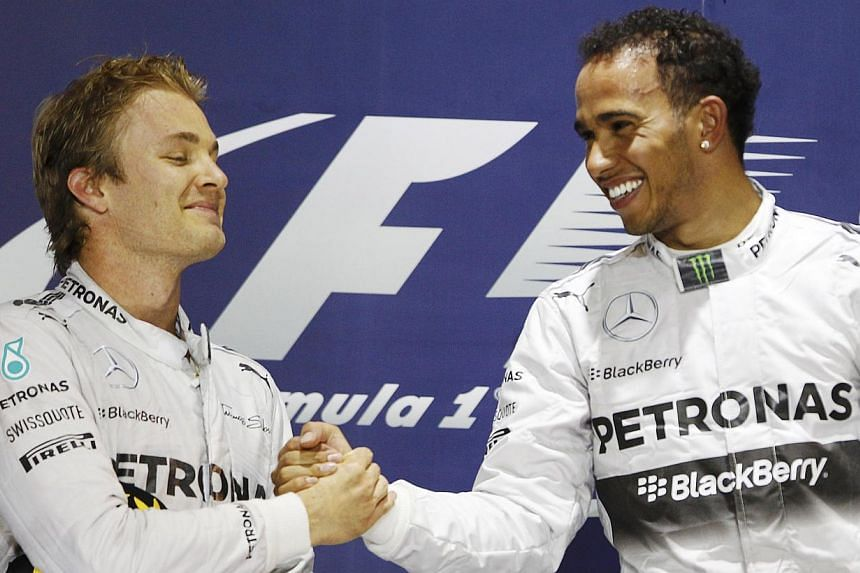 Mercedes Formula One driver Lewis Hamilton of Britain (right) is congratulated by teammate Mercedes Formula One driver Nico Rosberg of Germany on the podium after he won the Bahrain F1 Grand Prix at the Bahrain International Circuit (BIC) in Sakhir,