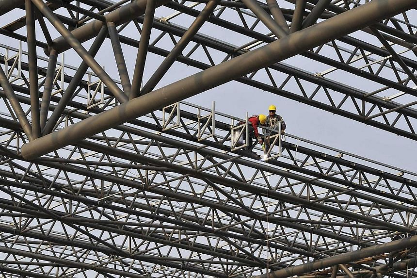 Labourers work at a construction site of a railway station in Hefei, Anhui province, on March 28, 2014.Growth in regional powerhouse China will ease to 7.6 per cent from 7.7 per cent as it undergoes structural reforms. -- PHOTO: REUTERS