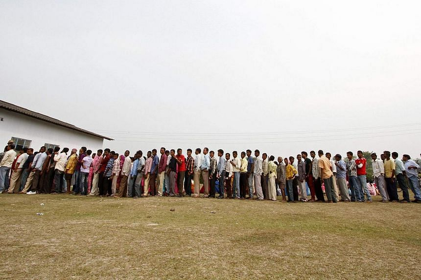 People line up to cast their vote outside a polling station at Dhekiajuli in Sonitpur district in the northeastern Indian state of Assam on April 7, 2014. The first Indians cast their votes in the world's biggest election on Monday with Hindu nationa