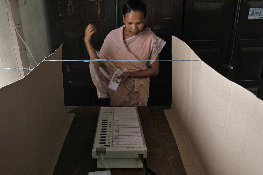 A woman prepares to cast her vote using an electronic voting machine inside a polling booth at Dhekiajuli in Sonitpur district in the northeastern Indian state of Assam on April 7, 2014. The first Indians cast their votes in the world's biggest elect