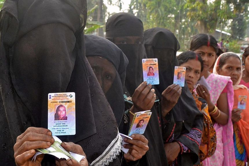 Indian Muslim voters pose with identification as they wait in line to vote outside a polling station in Koliabor, in Assam state's Nagoan district some 180km east of Guwahati, on April 7, 2014. Indians have begun voting in the world's biggest electio