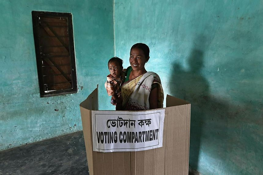 A woman holds her son as she casts her vote inside a booth at a polling station in Majuli, a large river island in the Brahmaputra river, Jorhat district, in the northeastern Indian state of Assam on April 7, 2014. The first electors cast their votes