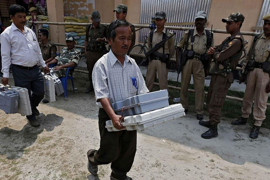 Election officials carry Electronic Voting Machines as Indian security personnel stand guard at a distribution centre ahead of general elections in Jorhat district, in the north-eastern Indian state of Assam on April 6, 2014. -- PHOTO: REUTERS
