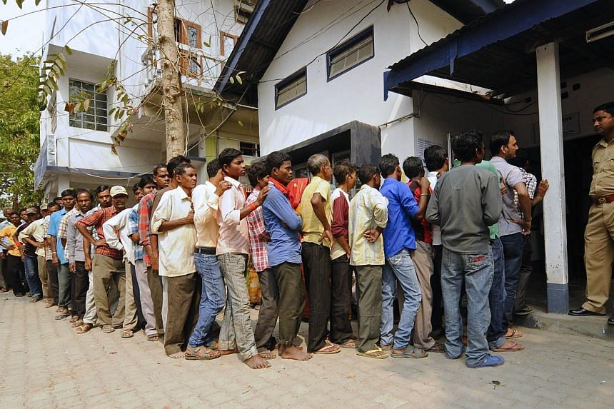 Indian voters waiting in line to vote outside a polling station at Dekhijuli, some 180km from Guwahati, the capital city of India's north-eastern state of Assam on April 7, 2014, during national elections. -- PHOTO: AFP