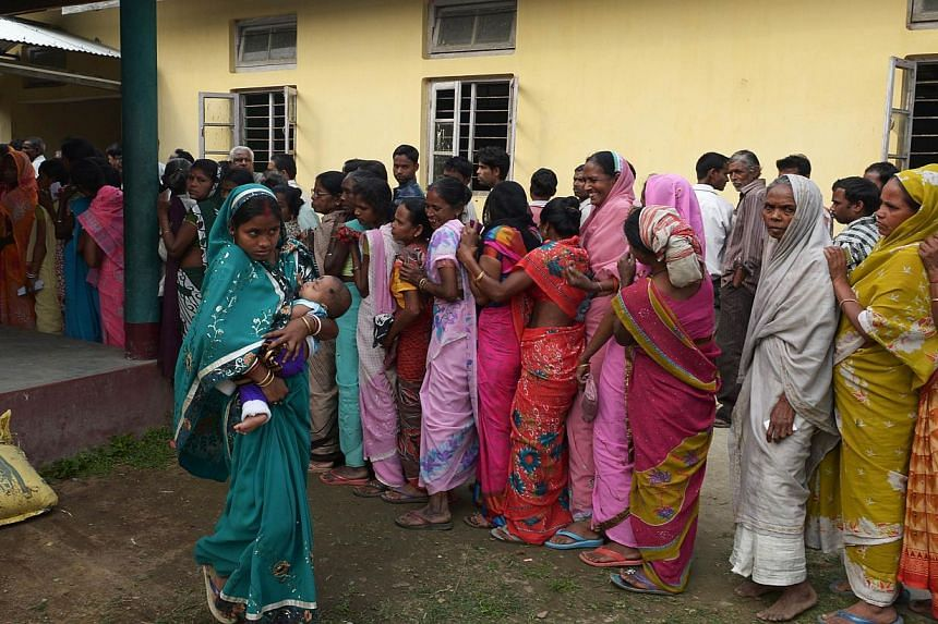 An Indian voter, seen carrying her child, walks past other voters waiting in line outside a polling stating after casting her vote in Dibrugarh on April 7, 2014, during national elections. -- PHOTO: AFP