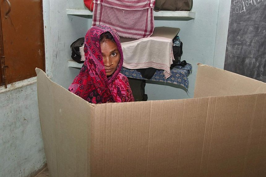 A woman looks on as she casts her ballot inside a polling station at Orang village in Sonitpur district in the north-eastern Indian state of Assam on April 7, 2014. -- PHOTO: REUTERS