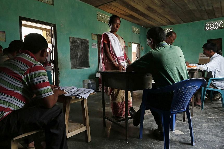 A woman (centre) waits to get her voter slip to cast her vote at a polling station in Majuli, a large river island in the Brahmaputra river, Jorhat district, in the north-eastern Indian state of Assam on April 7, 2014. -- PHOTO: REUTERS