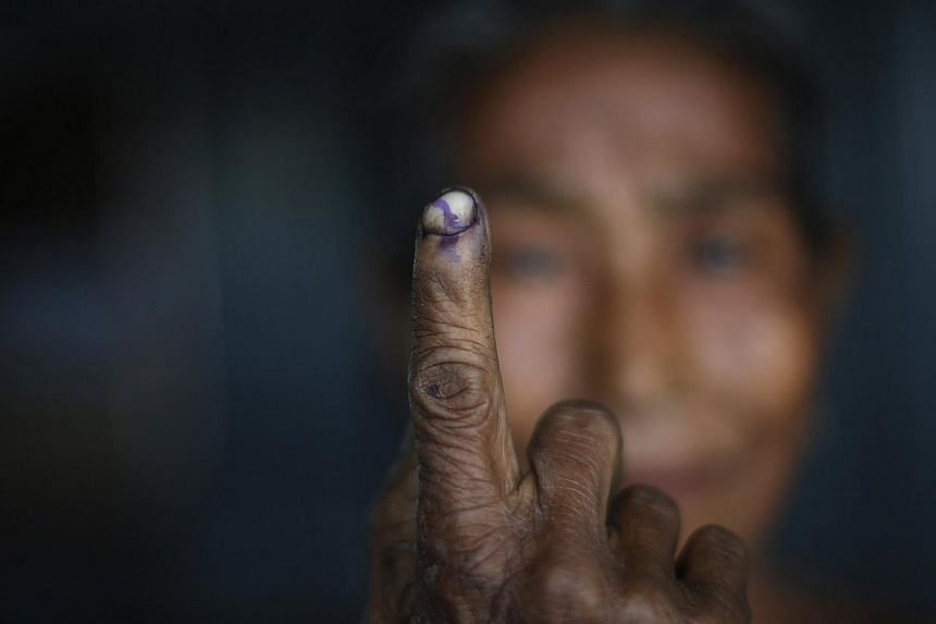 A woman shows her ink-marked finger after casting her vote at a polling station in Majuli, a large river island in the Brahmaputra river, Jorhat district, in the northeastern Indian state of Assam on April 7, 2014. -- PHOTO: REUTERS