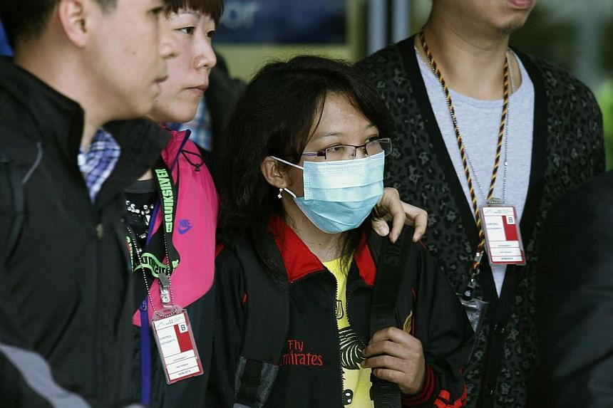 Indonesian domestic helper Erwiana Sulistyaningsih (centre), accompanied by Hong Kong Airport Authority personnel, walks out from a special exit upon her arrival at the Hong Kong Airport, on April 7, 2014. An Indonesian maid allegedly tortured by her