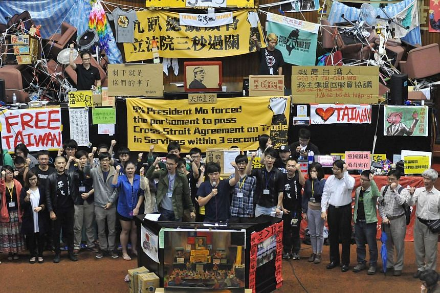 Students protest leaders Lin Fei-fan(front centre left) and Chen Wei-ting (front centre right) shout slogans during an occupy protest against a contentious trade agreement with China inside the Parliament building in Taipei, on April 7, 2014. -- PHOT