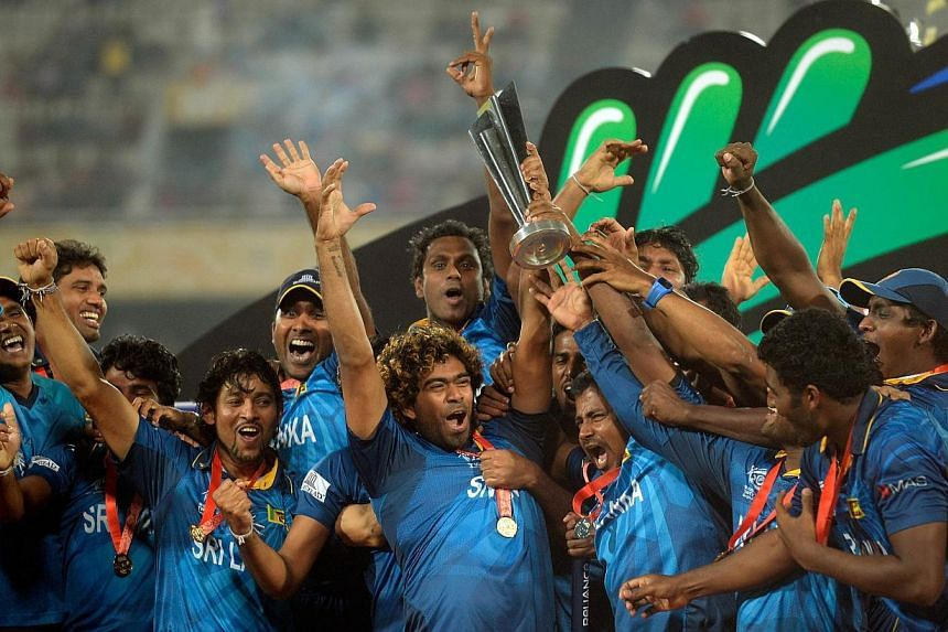 Sri Lanka cricketer Lasith Malinga holds up the winner's trophy as he celebrates with teammates after the ICC World Twenty20 cricket final match between India and Sri lanka at The Sher-e-Bangla National Cricket Stadium in Dhaka on April 6, 2014. -- P